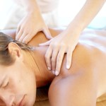 Masseuse Massaging Young Man Lying on Table Closed Eyes